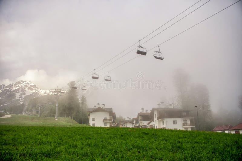 缆绳驾空滑车和瑞士山中的牧人小屋在雾 罗莎Khutor在夏天 库存照片
