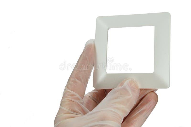 缎光白设计塑料灯开关框架在左手的手指举行了在透明乳汁安全手套,白色背景的 库存照片