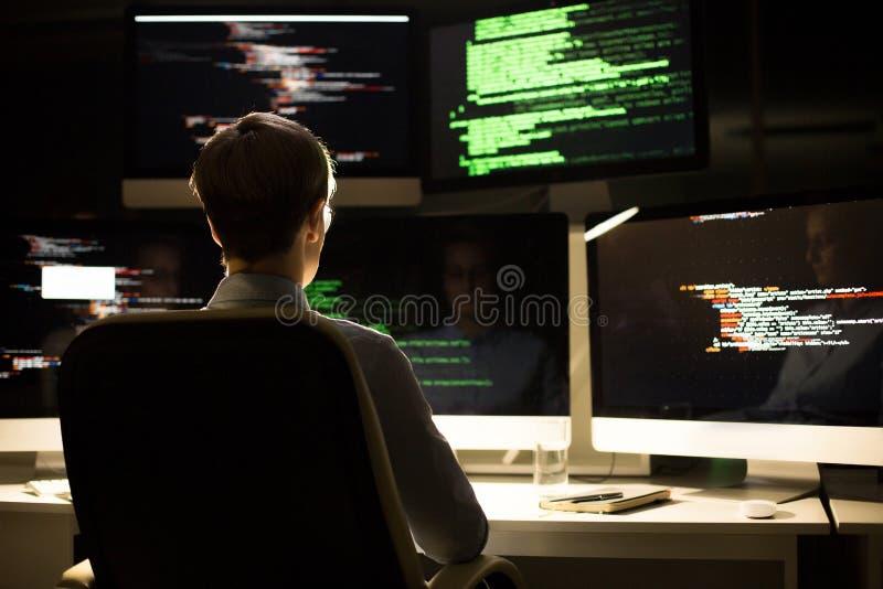 编制程序在昏暗的办公室 免版税库存图片