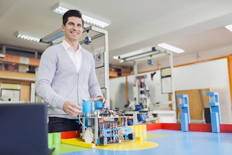 编程机器人的电机工程师在机器人学课期间 库存照片