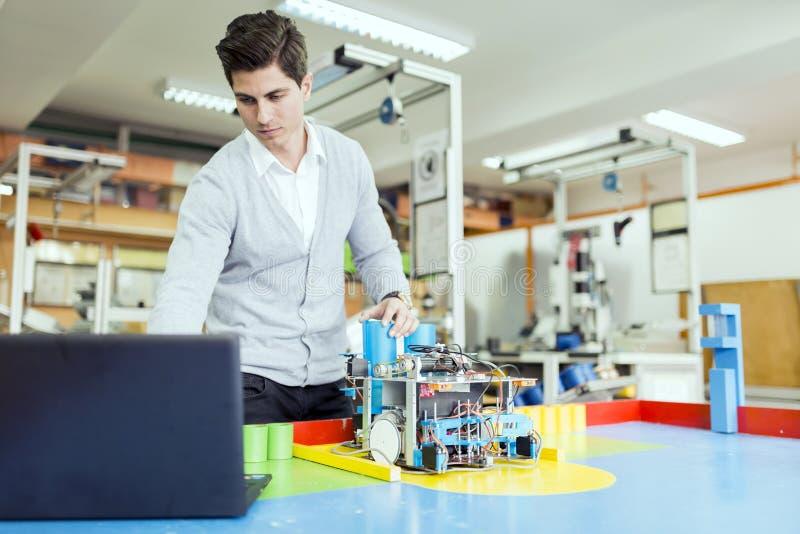 编程机器人的电机工程师在机器人学课期间 图库摄影