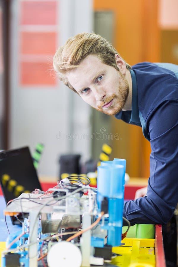 编程机器人的电机工程师在机器人学课期间 免版税库存图片