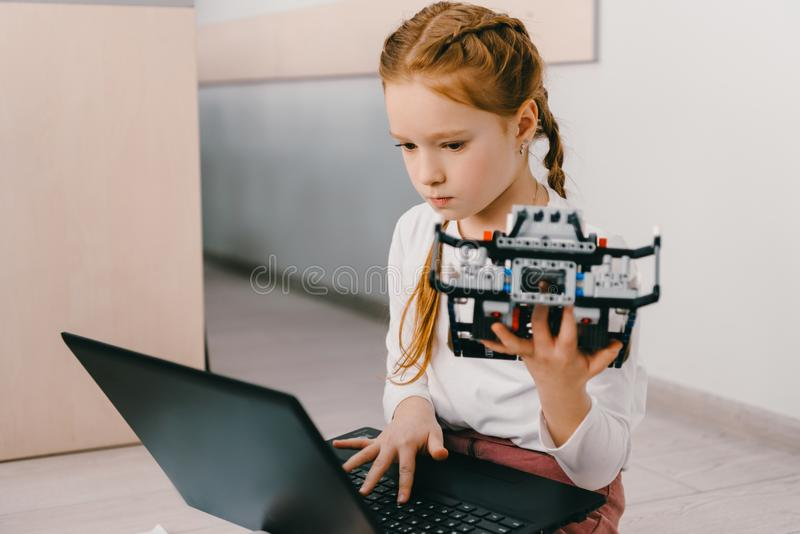 编程diy机器人,词根的美丽的被集中的孩子 库存图片