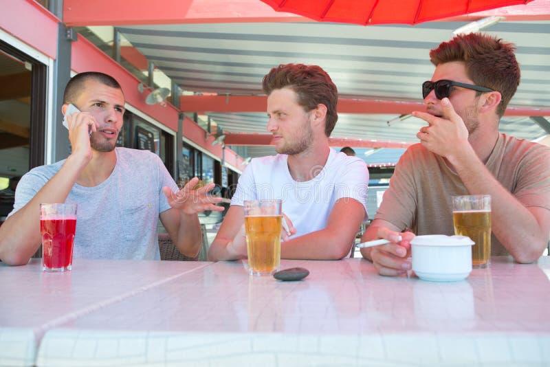 编组一起喝啤酒的朋友在室外酒吧 库存照片