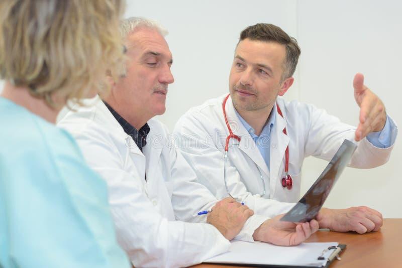 编组遇见和采取笔记的医生在医疗办公室 库存图片