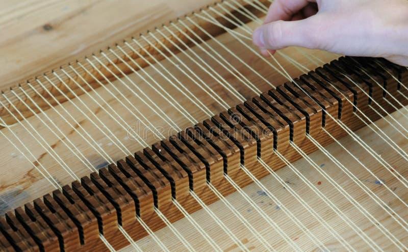编织在织布机框架 特写镜头妇女` s手在编织的框架投入螺纹 库存照片