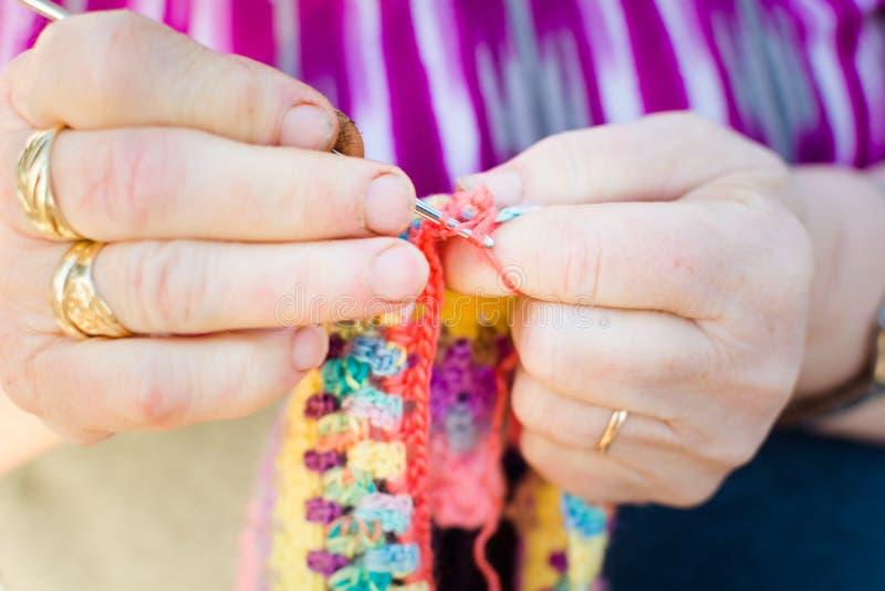 编织在编织针的一个老妇人的手特写镜头,使用五颜六色的羊毛 免版税库存图片