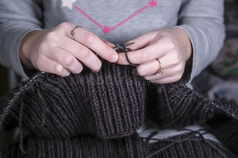 编织在金属编织针的女孩 免版税库存照片