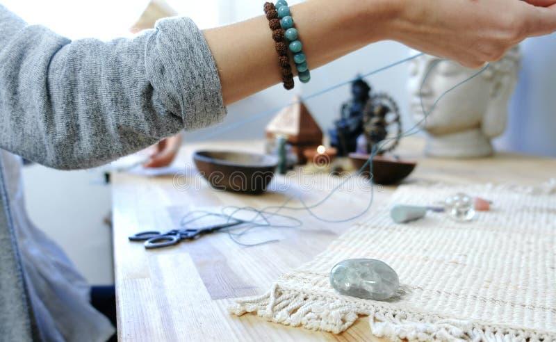 编织小珠 妇女` s的特写镜头在车间递串起在螺纹的小珠,做首饰 免版税库存照片