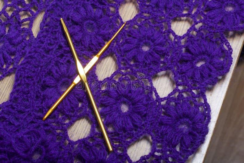 编织的勾子以一个被编织的紫罗兰色钱包为背景 免版税库存照片