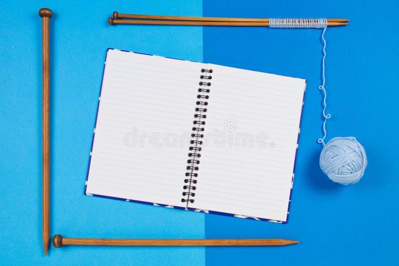 编织针,蓝色毛线球和打开在蓝色背景的纸笔记本 免版税库存照片