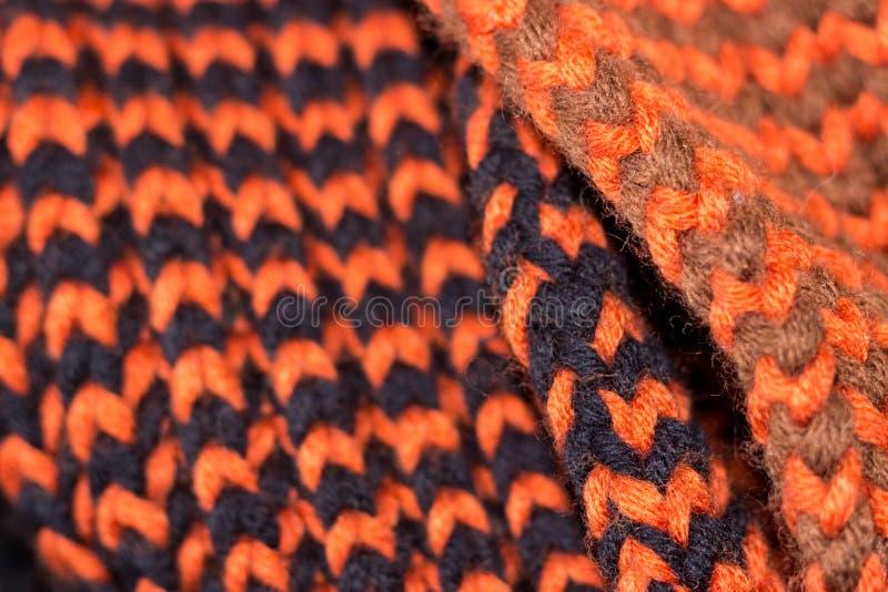 编织 背景被编织的纹理 明亮的编织针 编织的橙色和黑毛纱 免版税库存图片