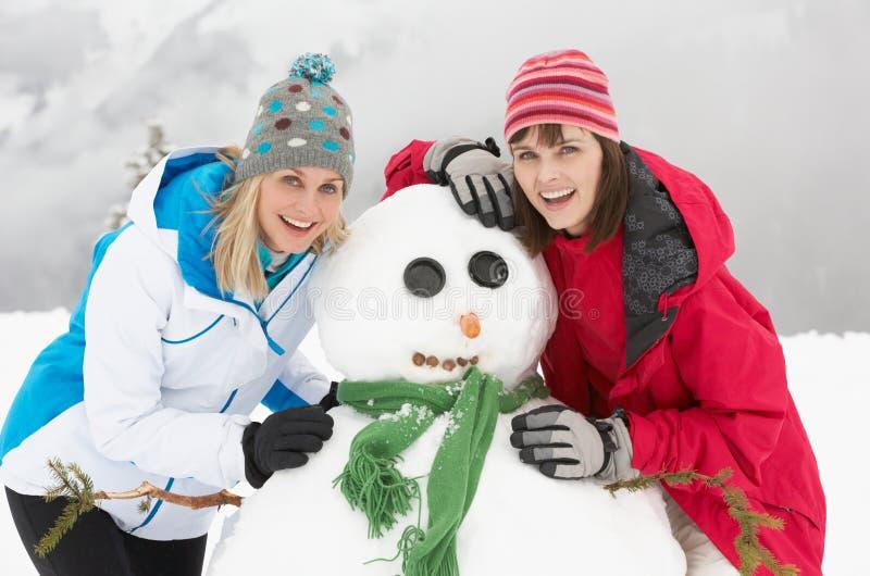 编译在滑雪节假日的二个女性朋友雪人 库存照片