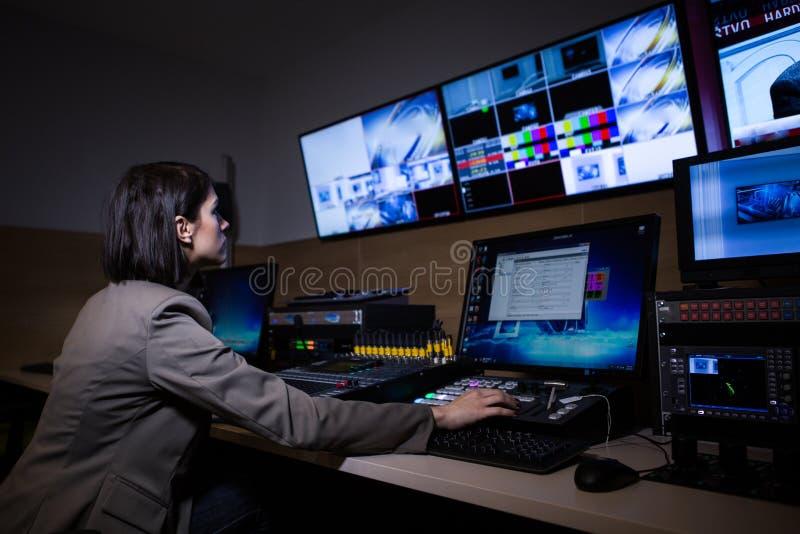 编辑的电视主任在演播室 电视主任谈话与在电视广播画廊的视觉搅拌器 妇女坐在视觉mixin 免版税库存照片