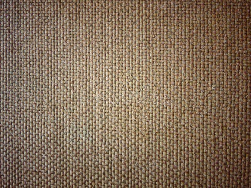 编辫子的米黄布料地毯,形成一个相当方格的样式 免版税库存图片