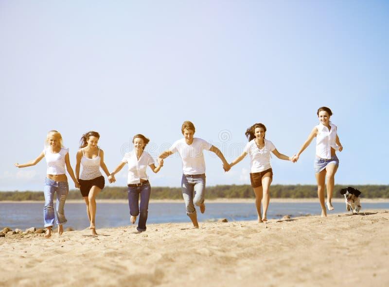 编组享受一个海滩党的年轻朋友在度假 人们h 免版税库存照片