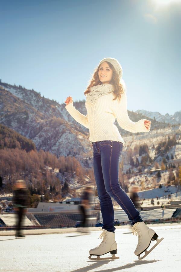 编组滑稽少年女孩滑冰室外在滑冰场 库存图片