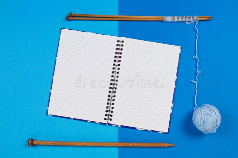编织针,蓝色毛线球和打开在蓝色背景的纸笔记本 图库摄影