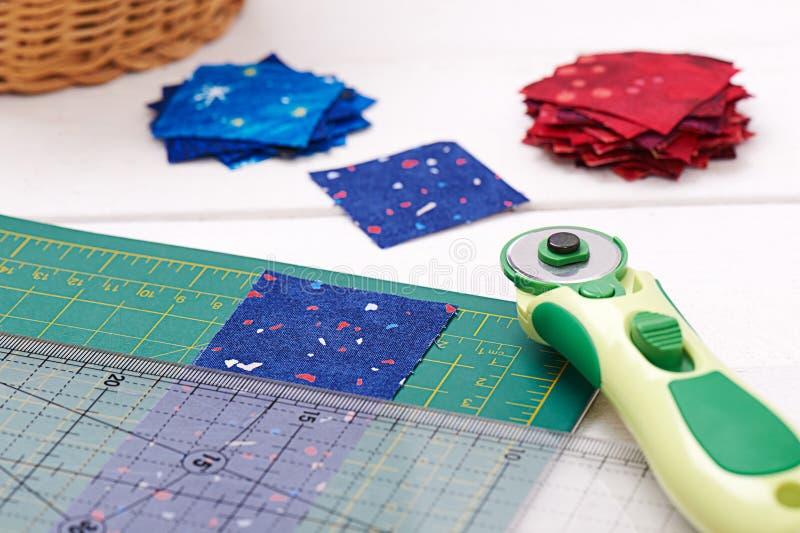 缝制的工具,织品片断准备对切开,两堆被切除织品 免版税库存照片