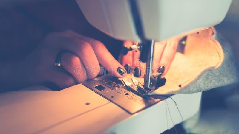 缝合在缝纫机的妇女手织品 图库摄影