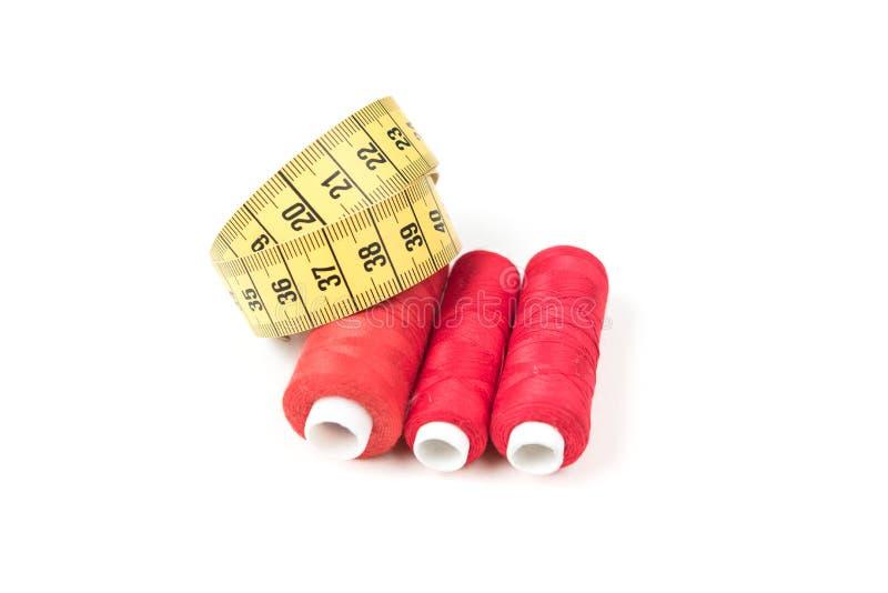 缝合的供应、红色螺纹在白色卷和黄色测量的磁带有黑数字的在白色背景 剪裁供应 免版税图库摄影