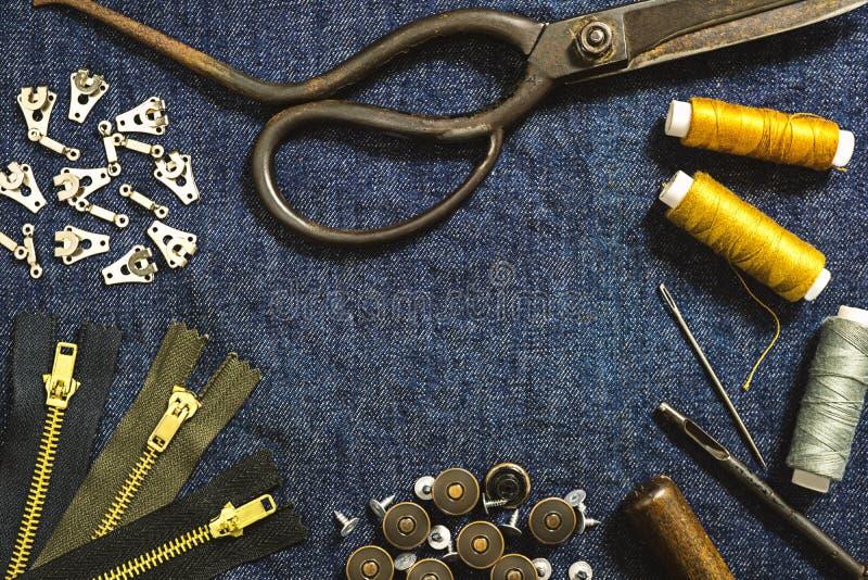 缝合的工具平的位置为牛仔裤牛仔布织品的穿衣 免版税图库摄影