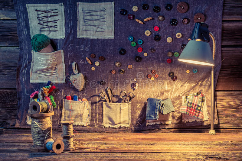 缝合的布料由螺纹、针和按钮制成在裁缝车间 皇族释放例证