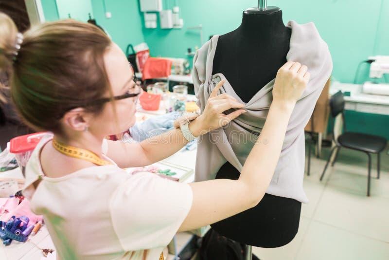 缝合的车间 拿着评定裁缝工作的现有量 工作在礼服的年轻裁缝在演播室 库存照片