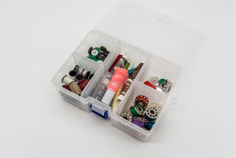 缝合的辅助部件和在白色隔绝的螺纹无危险塑料盒 库存照片