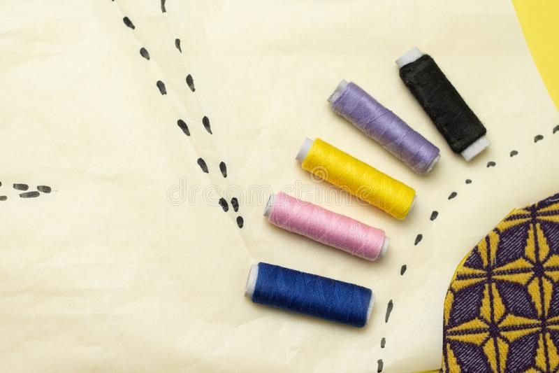 缝合的辅助部件和织品在yelow背景 缝合针线、别针、样式和缝合的厘米 对在家缝合 ?? 免版税库存图片