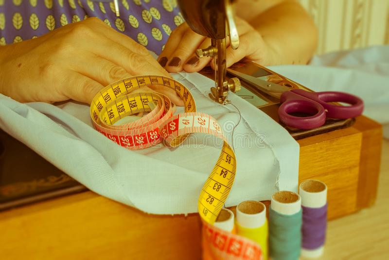 缝合的过程,缝纫机缝合妇女缝合橡皮防水布的` s手 免版税图库摄影