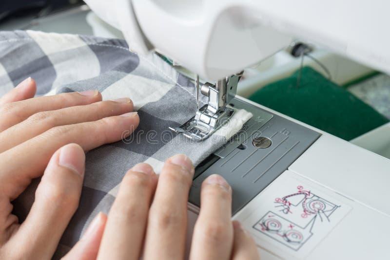 缝合的过程,缝纫机缝合缝合橡皮防水布的妇女的手 免版税库存照片