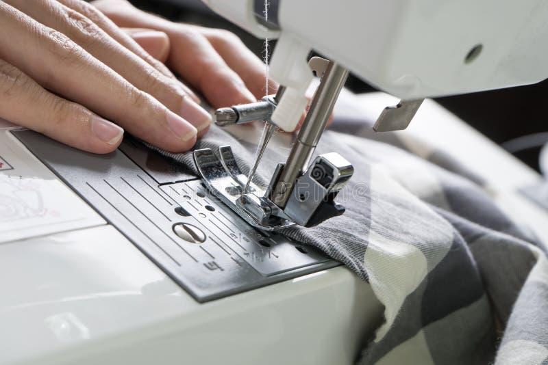 缝合的过程,缝纫机缝合缝合橡皮防水布的妇女的手 免版税库存图片