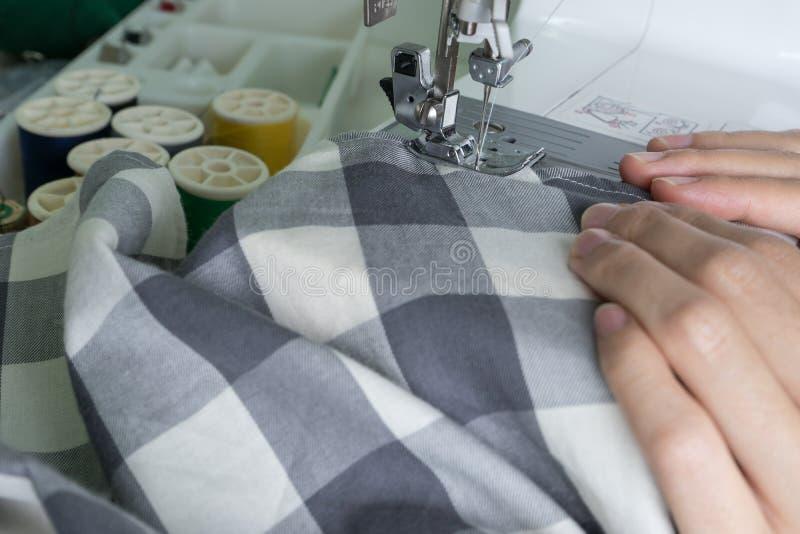 缝合的过程,缝纫机缝合缝合橡皮防水布的妇女的手 免版税图库摄影