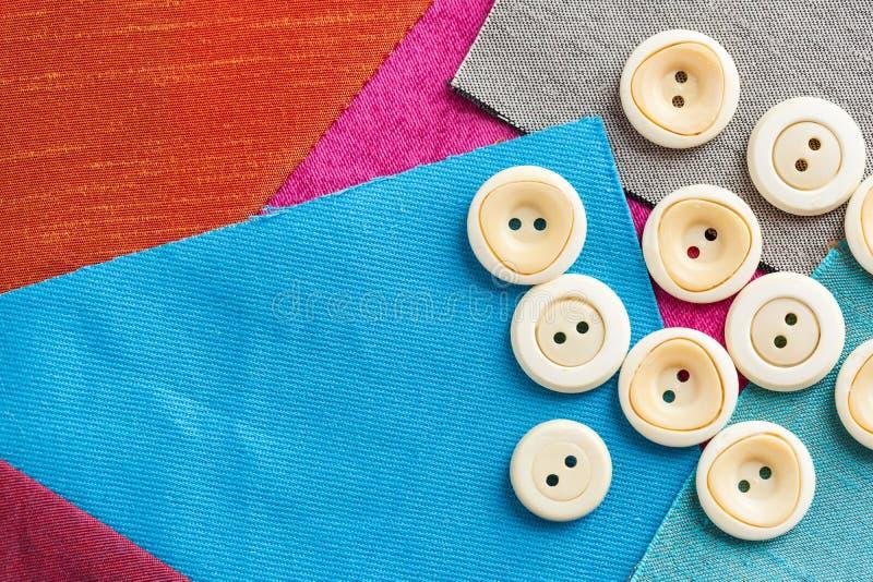 缝合,补缀品,剪裁和时尚概念-在套的特写镜头针线的白色按钮在背景  免版税库存照片