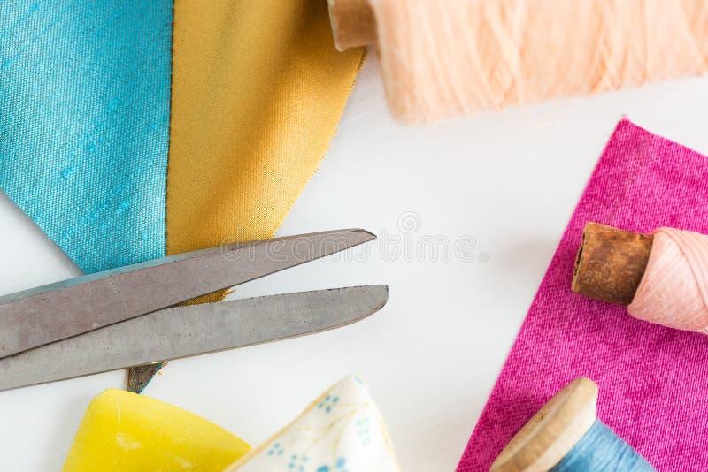 缝合,补缀品,剪裁和时尚概念-在白色工作书桌上的特写镜头工具在演播室,剪刀,蓝色短管轴  库存图片