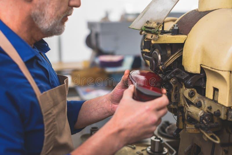 缝鞋类的脚底的工匠 库存照片