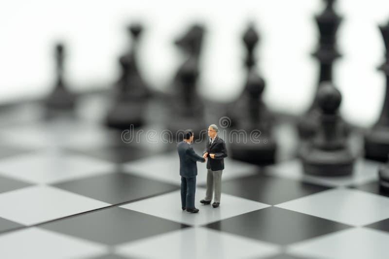 缩样2人商人握手在一杆棋枰的有在谈判在事务的后面的一个棋子的 作为背景 免版税库存图片