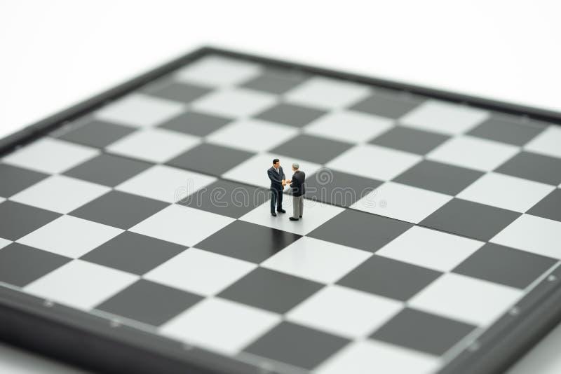 缩样2人商人握手在一杆棋枰的有在谈判在事务的后面的一个棋子的 作为背景 库存照片