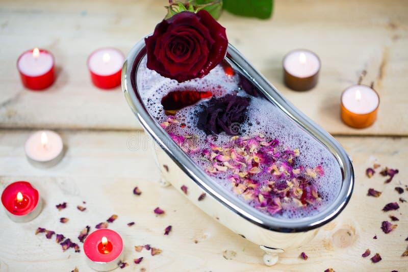 浴缸用玫瑰和玫瑰花瓣,一点浴缸填装了 免版税库存照片