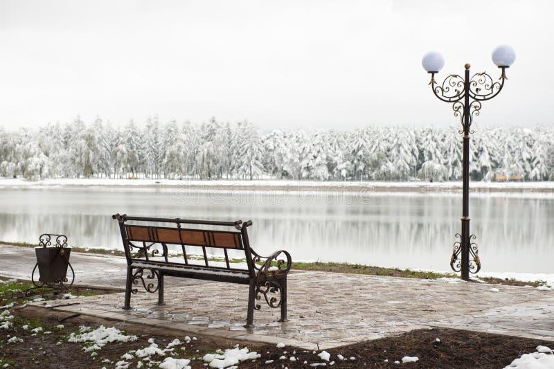缸长凳和灯笼在冬天公园和湖的背景 库存照片
