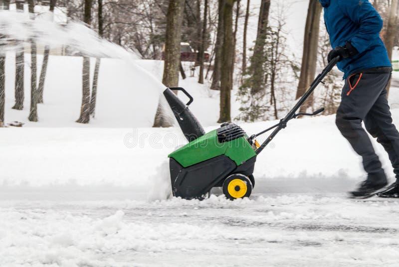 缺少,NJ,美国- 2019年1月13日:在降雪和冰以后在行动的吹雪机被推挤的在一寒冷冬天天 库存照片