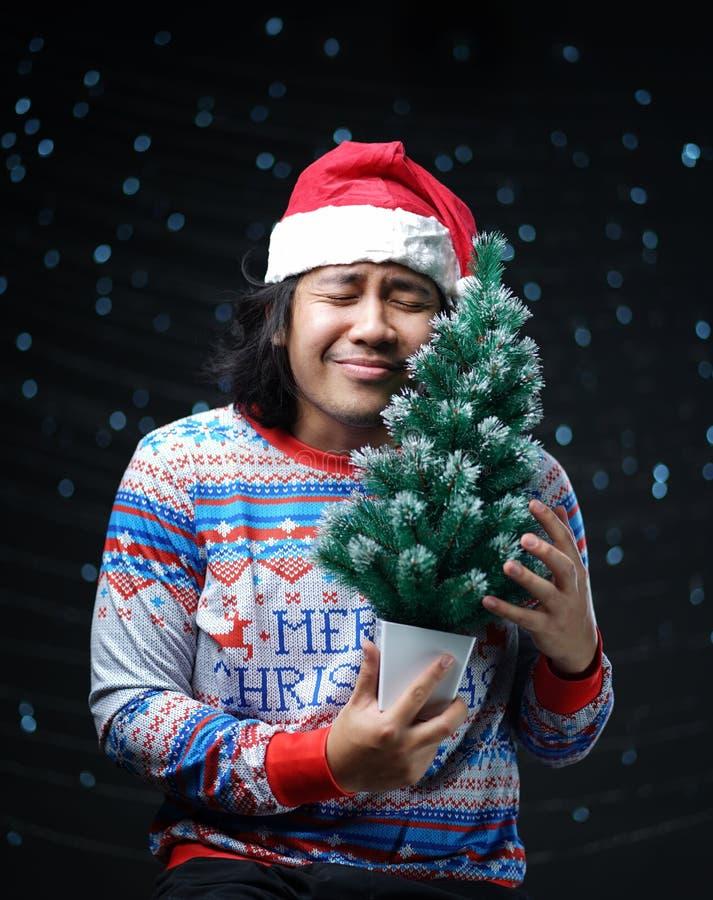缺掉圣诞节片刻概念 拥抱小基督的亚裔人 免版税库存照片