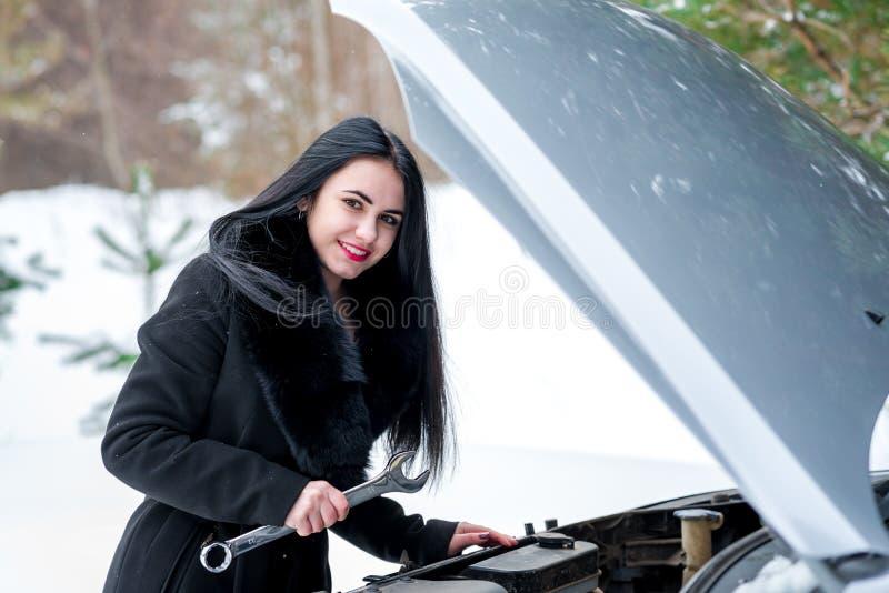 缺点汽车在冬天 设法年轻美丽的女孩修理t 免版税库存照片
