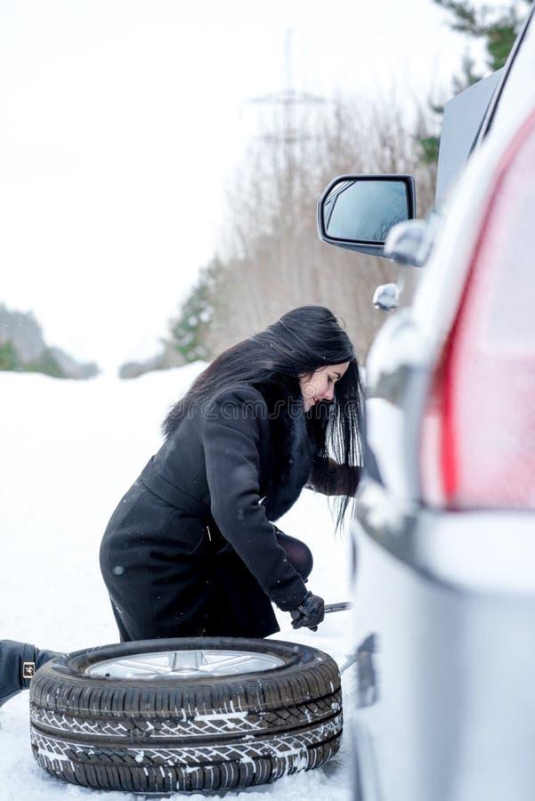 缺点汽车在冬天 设法年轻美丽的女孩修理t 图库摄影