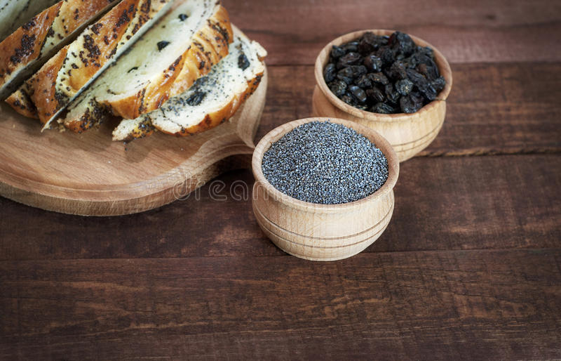 罂粟种子和葡萄干在木碗棕色表面上 库存照片