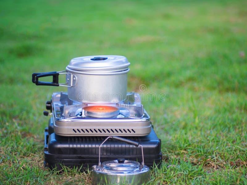 罐在便携式的煤气炉站立 烹调在野营的概念 库存图片