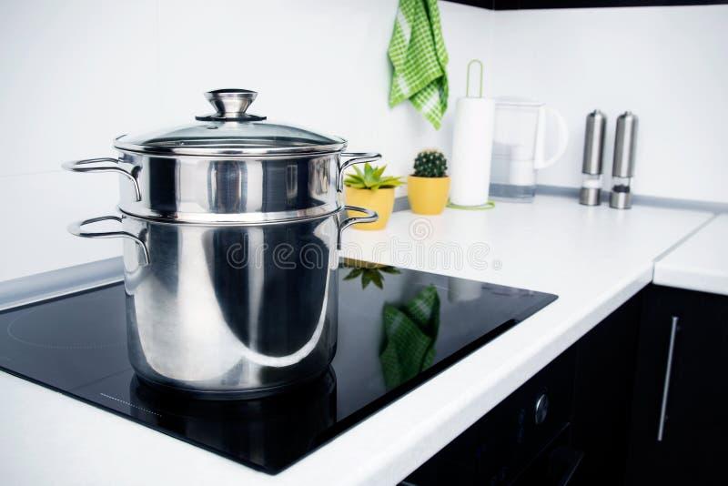 罐在有归纳火炉的现代厨房里 库存图片