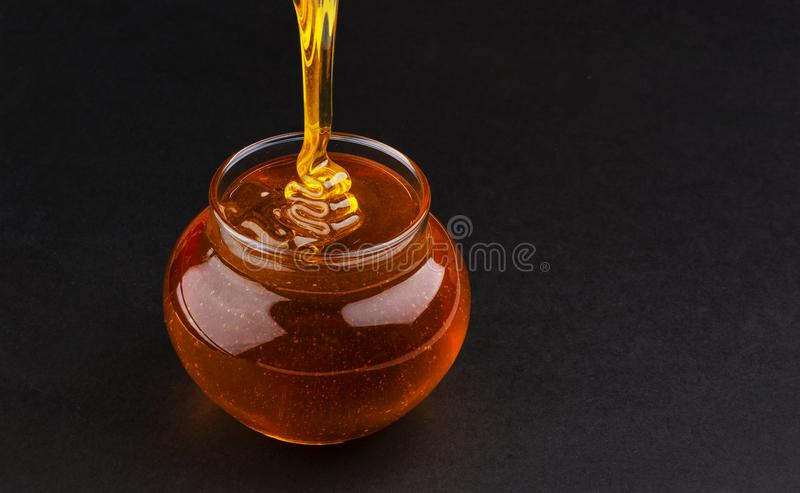 罐在黑背景的倾吐的蜂蜜与拷贝空间 免版税库存照片