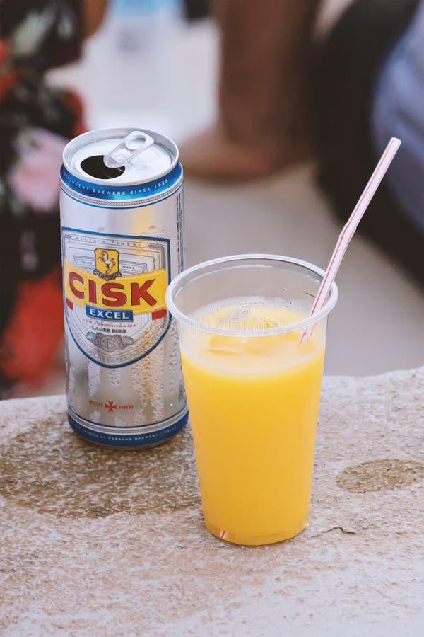 罐头马尔他地方Cisk啤酒贮藏啤酒和橙汁过去在塑料杯子 免版税库存图片